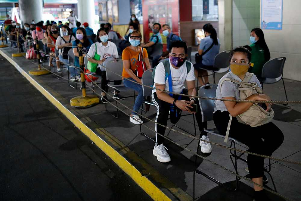 Passengers wearing masks for protection against Covid-19 maintain social distancing while queueing to ride a bus in Manila, Philippines July 14, 2020. —  Reuters pic