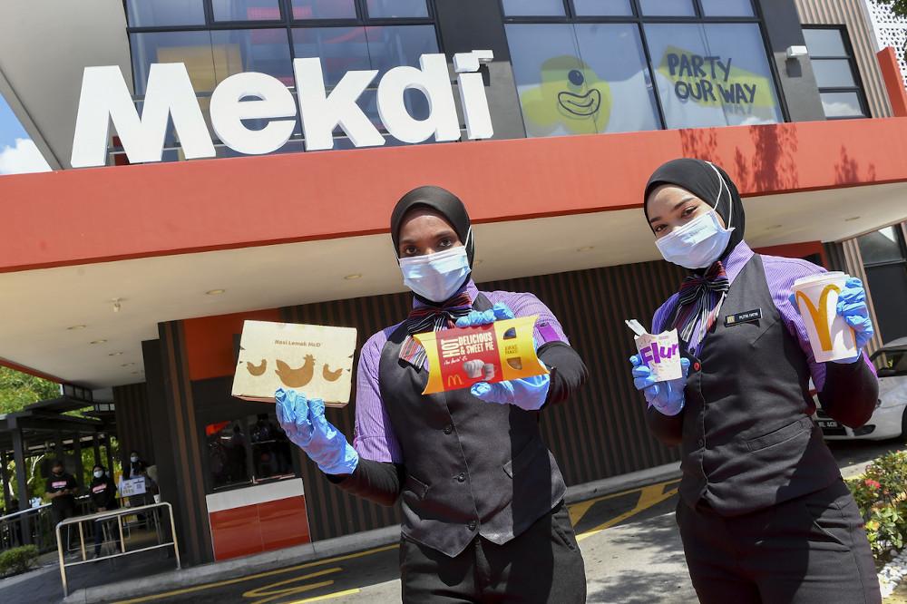 McDonald's Putrajaya crew Putri Fatin Fatiqah Roslee and Shahrul Syalili Mat Sharif at the launch of the 'Mekdi' signboard in conjunction with Merdeka Day and Malaysia Day in Putrajaya August 26, 2020. — Bernama pic