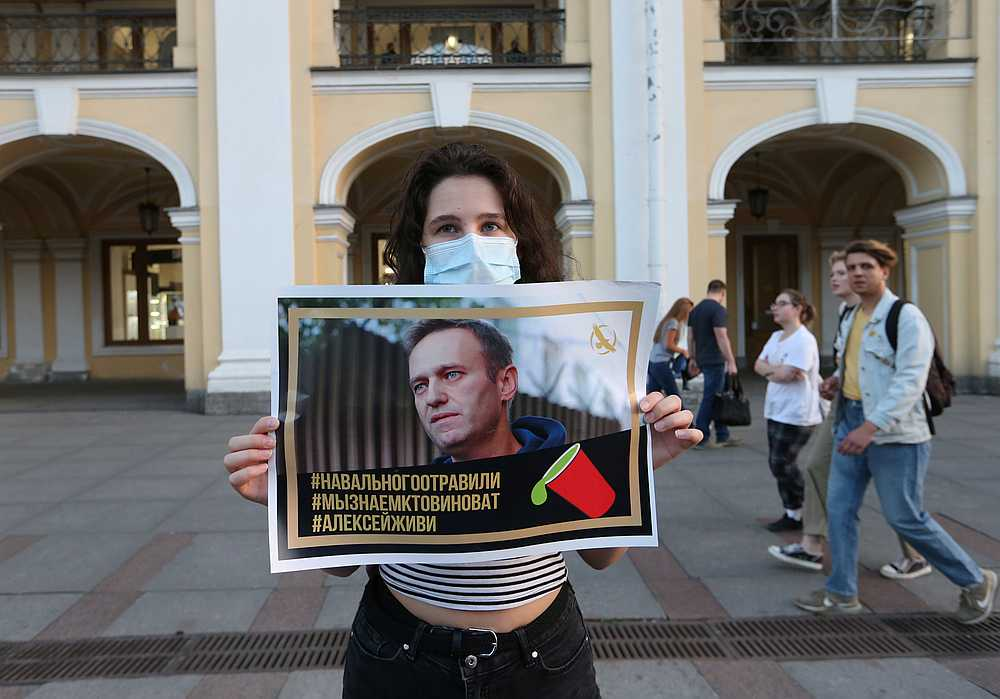 A woman at a gathering to show support for Russian opposition leader Alexei Navalny, in Saint Petersburg, Russia August 20, 2020. The placard reads 'Navalny was poisoned. We know who is to blame. Alexei, live.' — Reuters pic