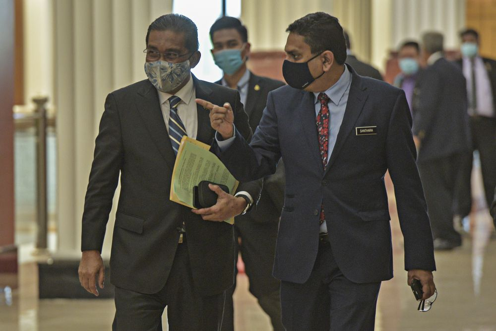 Minister in the Prime Minister's Department Datuk Takiyuddin Hassan (left) is pictured in Parliament, Kuala Lumpur August 27, 2020. — Picture by Shafwan Zaidon