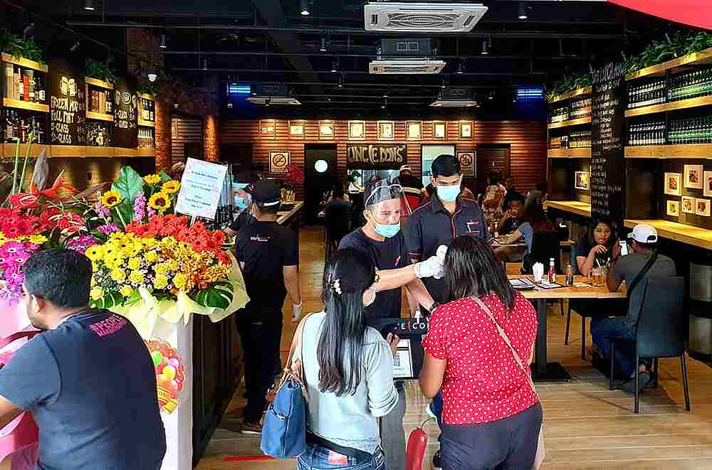 Staff taking the temperature of customers visiting the newly-opened Uncle Don's in Seremban. — Picture courtesy of Ian Ong
