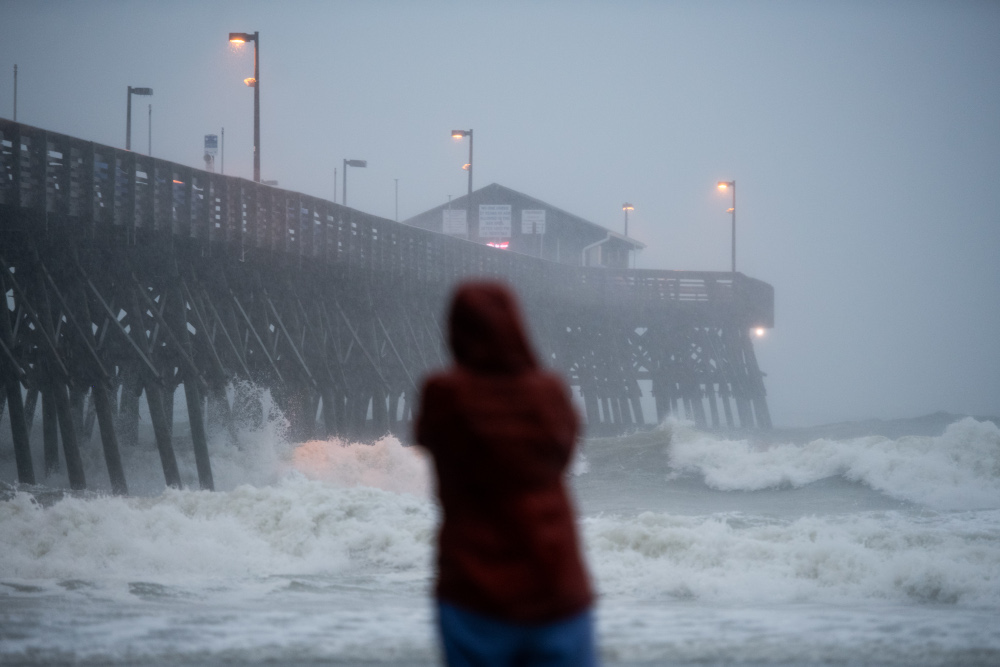 A person watches waves crashing against the Pier at Garden City August 3, 2020 in Garden City, South Carolina. — Sean Rayford/Getty Images North America/Getty Images via AFP