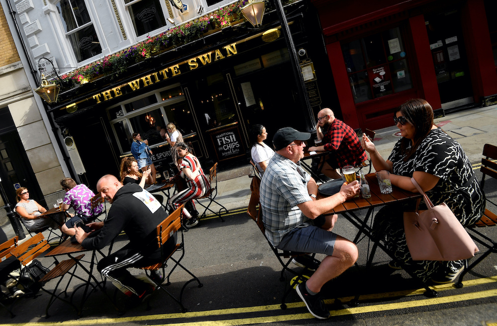 People drink outside a pub at the Covent Garden shopping and dining district, amid the spread of Covid-19), in London, Britain, August 2, 2020. — Reuters pic
