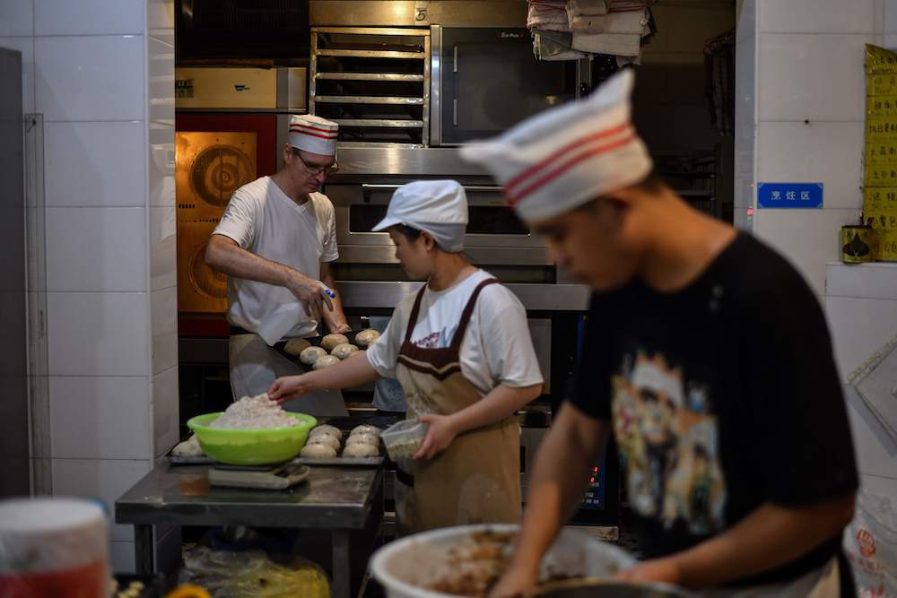 This photo taken on September 8, 2020 shows Uwe Brutzer (back left) working with hearing-impaired employees at his bakery in the city of Changsha. — AFP pic