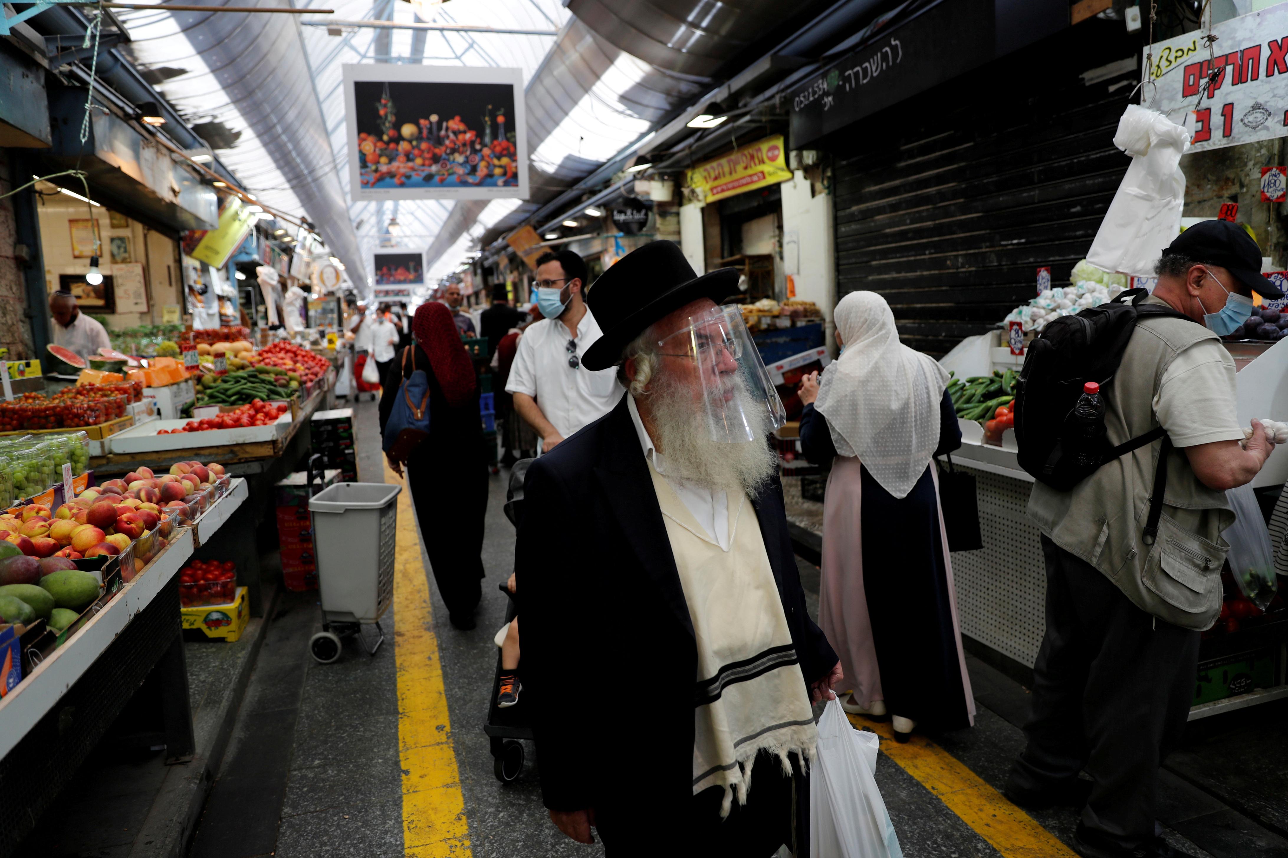 以色列7月再次爆发疫情。图示耶路撒冷居民到市场采买日用品时都戴上口罩或面罩。-路透社-