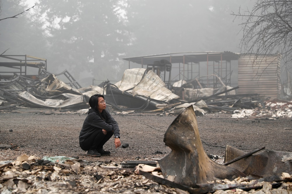 A woman inspects the remains of the burnt down property of her relatives, as the wildfire continues in Estacada, Oregon September 13, 2020. — Reuters pic