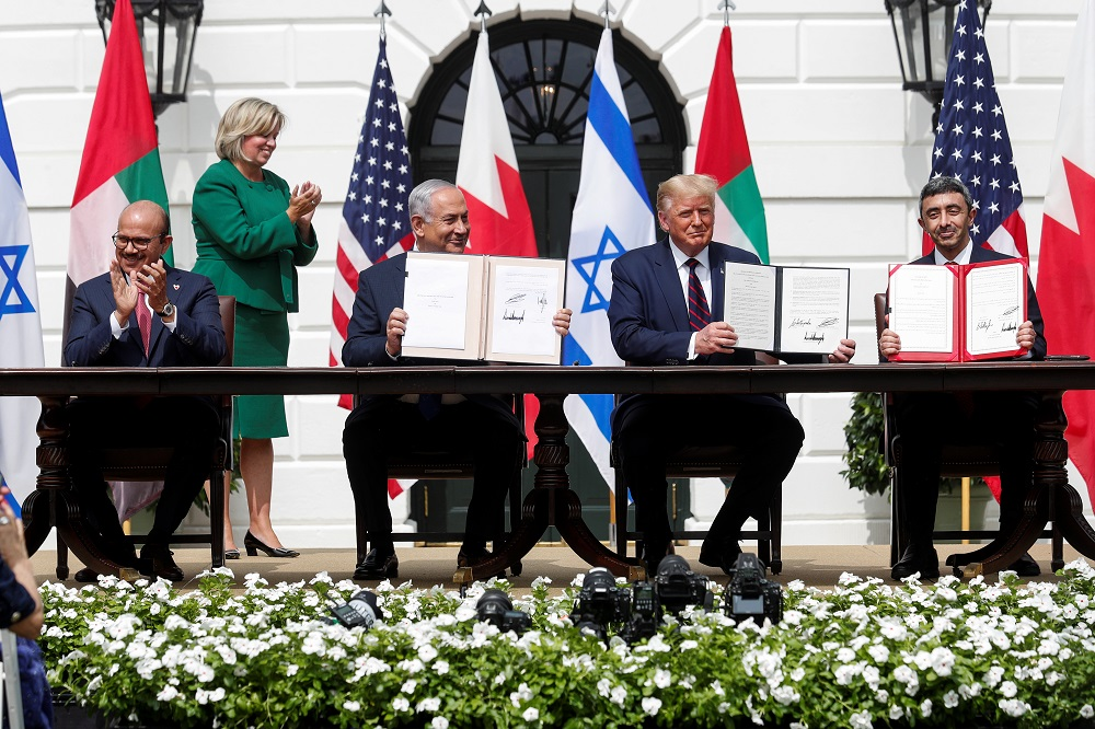 Bahrain's Foreign Minister Abdullatif Al Zayani, Israel's Prime Minister Benjamin Netanyahu and UAE Foreign Minister Abdullah bin Zayed display their copies of signed agreements while US President Donald Trump looks on as they participate in the signing ceremony of the Abraham Accords in Washington September 15, 2020. — Reuters pic