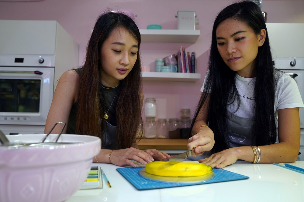 Cony and Alison, co-owners of Dear Harley Cake Studio, colour their banana illusion cake in Hong Kong August 25, 2020. — Reuters pic