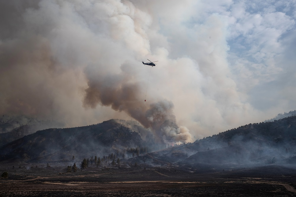 A helicopter carries water to the Brattain Fire smoke rises from the Fremont National Forest in Paisley, Oregon September 18, 2020. — Reuters pic