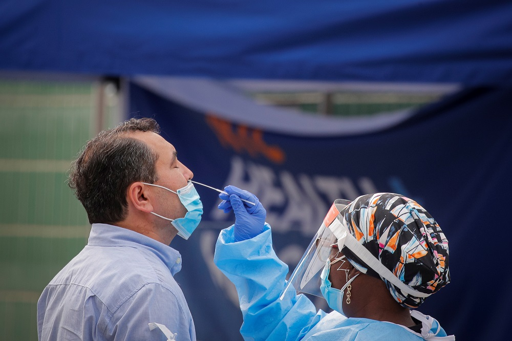 A health worker takes a swab sample from a man to test for the coronavirus disease in the Borough Park area of Brooklyn, New York September 25, 2020. — Reuters pic