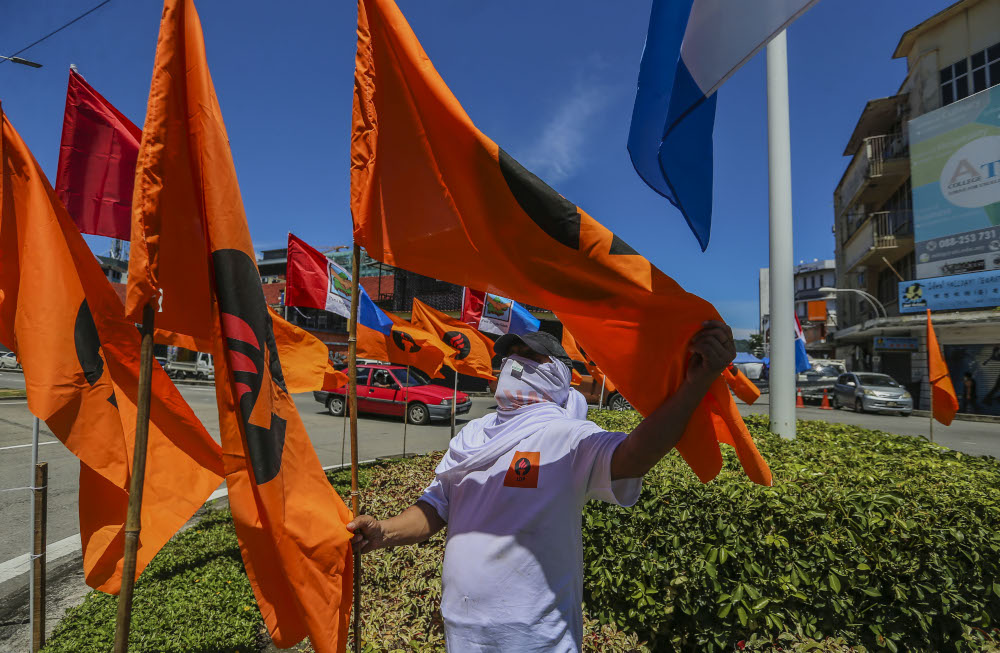 A worker installs a Liberal Democratic Party (LDP) flag in Kota Kinabalu, Sabah September 13, 2020. — Picture by Firdaus Latif