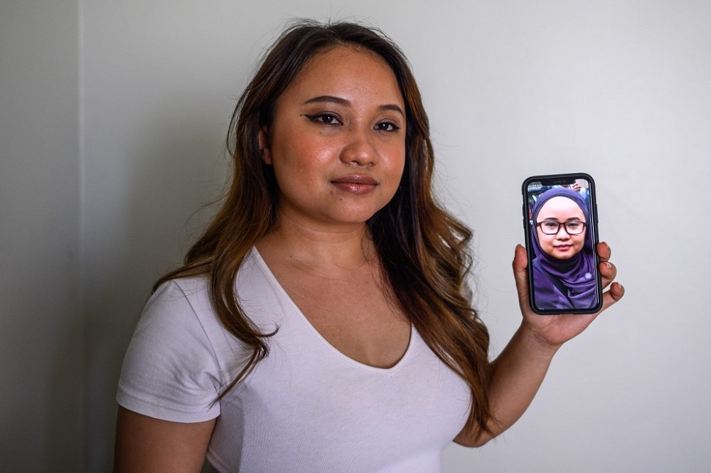 Maryam Lee posing with a picture on a mobile phone of her wearing a headscarf in her parent's home in Shah Alam August 17, 2020. — AFP pic