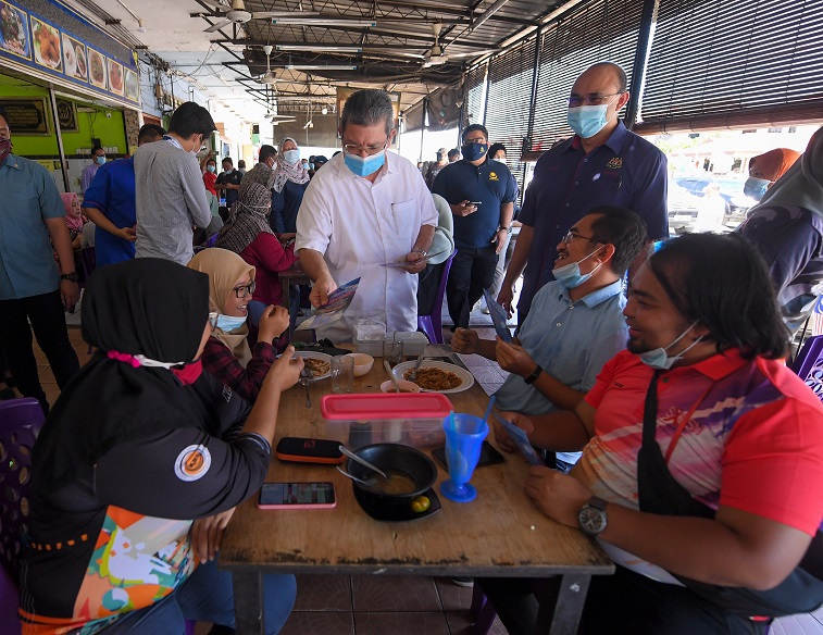 Communications and Multimedia minister Datuk Saifuddin Abdullah distributes the 'Let's Vote' pamphlets during the Info on Wheels Programme at Taman Jumbo, Putatan yesterday. — Bernama pic