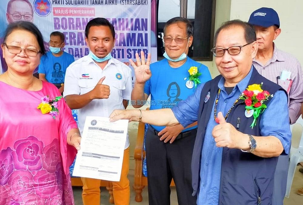 Datuk Anita Baranting (left) handing over the membership application form to Jeffrey (right). — Borneo Post Online pic