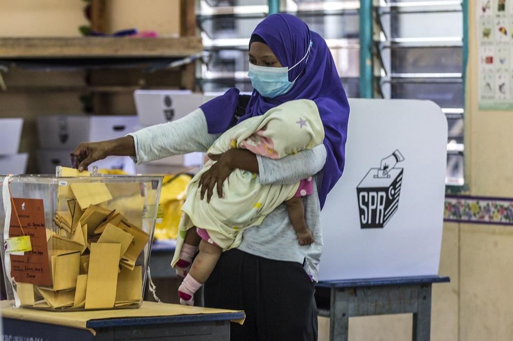 A voter cradles her child as he casts her vote at SK Pulau Gaya September 26, 2020.