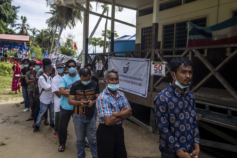 Voters wearing protective masks queue up to cast their votes during the Sabah state election in SK Pulau Gaya September 26, 2020.