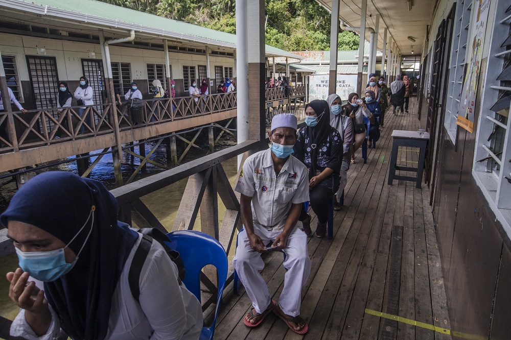 Voters wearing protective masks queue up to cast their votes during the Sabah state election in SK Pulau Gaya September 26, 2020. — Pictures by Firdaus Latif