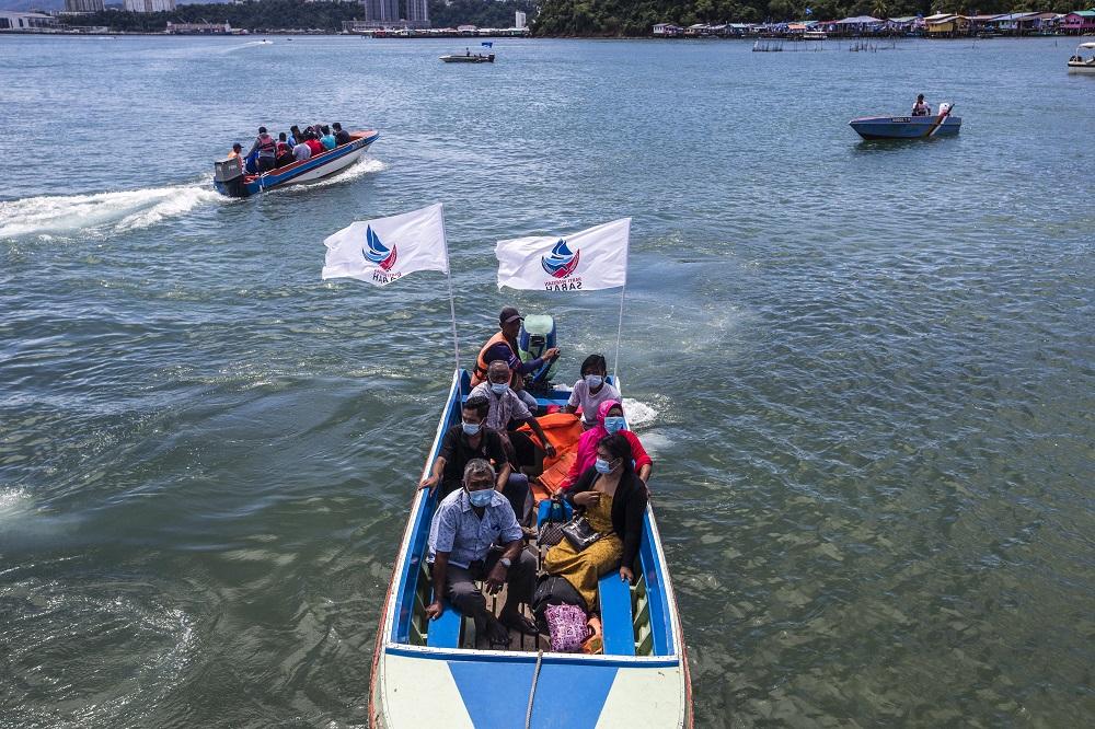 Voters arrive at polling station in SK Pulau Gaya by boat September 26, 2020.
