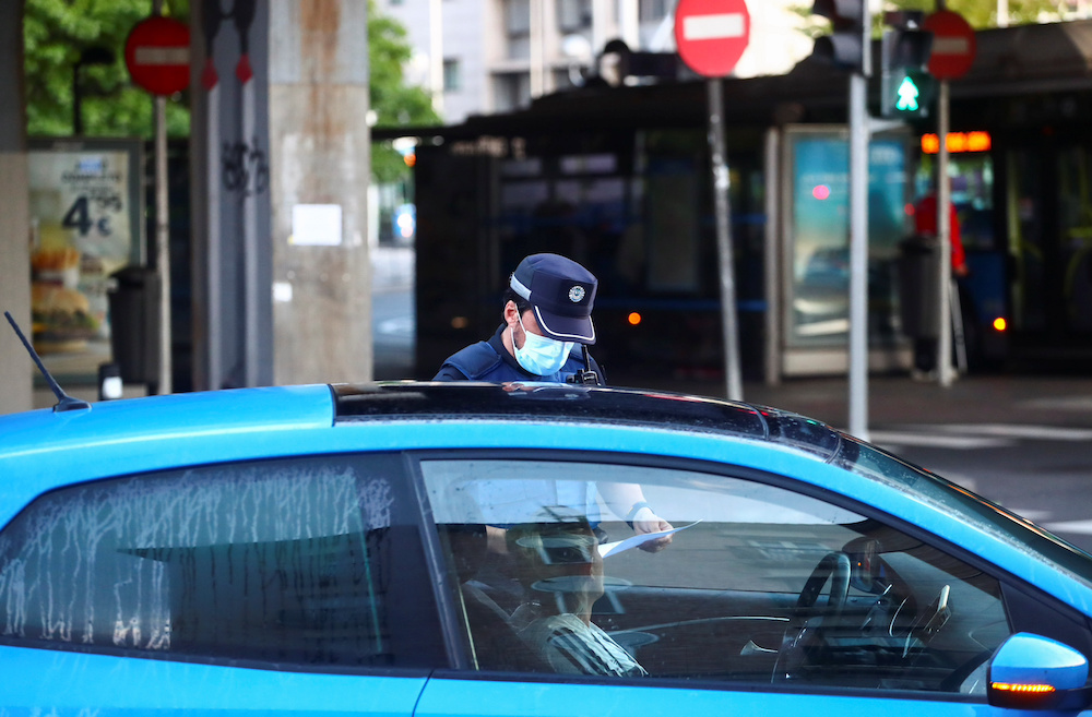 A local police officer checks documents at a traffic control point during the first day of a partial lockdown between and within areas in six districts amid the outbreak of the coronavirus disease (Covid-19) in Madrid, Spain, September 21, 2020. — Reute
