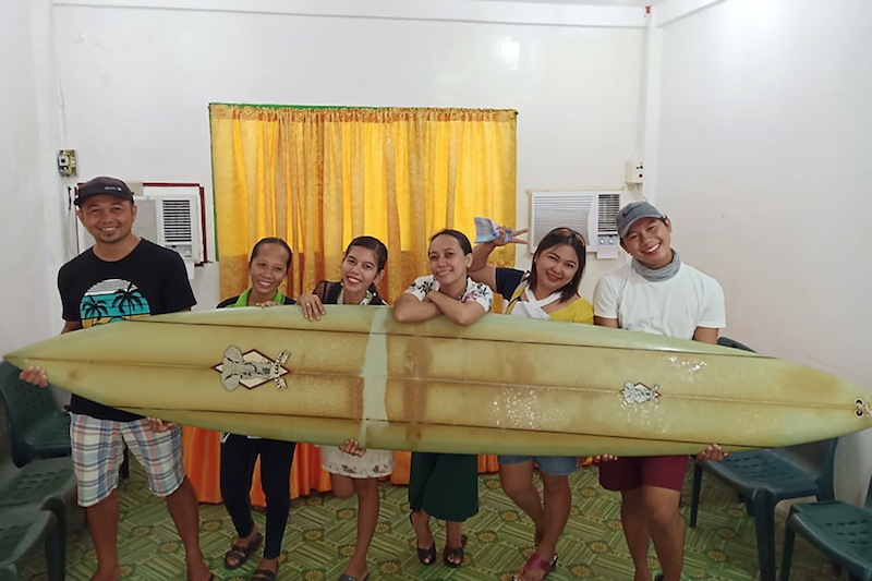 Filipino teacher Giovanne Branzuela (left) poses with his surfboard, once owned by surfer Doug Falter who lost it while surfing in Hawaii, along with his villagemates on Sarangani island in the Philippines. — Picture courtesy of Giovanne Branzuela via AFP