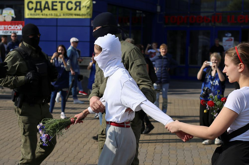 A Belarusian law enforcement officer detains a woman during an opposition rally to reject the presidential election results and to protest against the inauguration of President Alexander Lukashenko in Minsk, Belarus September 26, 2020. — Tut.By via Reuters