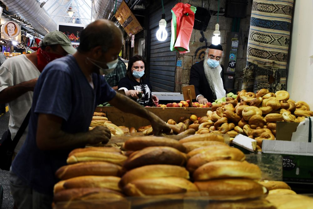 Customers wearing protective face masks shop at a food market as Israel is set to tighten its second nationwide coronavirus disease (Covid-19) lockdown amid a rise in infections, in Jerusalem September 24, 2020. — Reuters pic