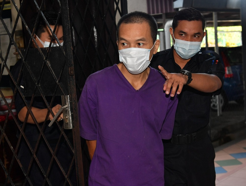 Pang Kar Foong (centre) is led to the Magistrate's Court in Ipoh September 21, 2020. — Bernama pic