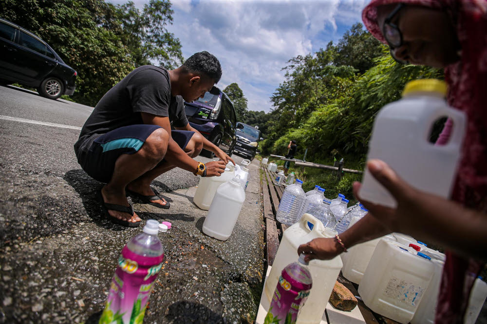 A general view of some residents seen collecting hill water as an alternative measure after facing water supply disruption during a survey in Jalan Ulu Yam on September 6, 2020. — Picture by Hari Anggara