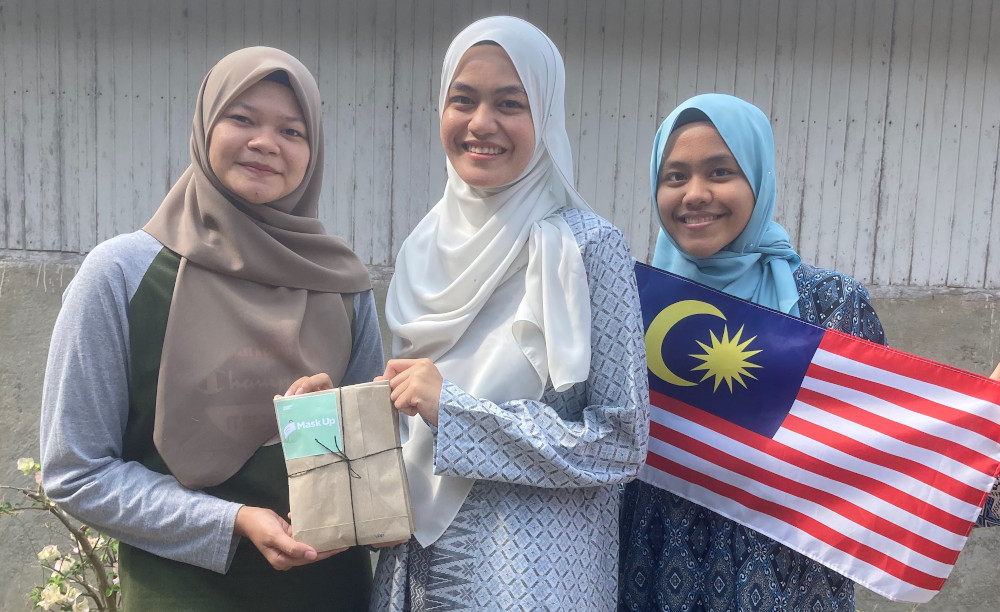 Absarina Zakaria (centre) and Raudhah Zakaria (right) distributing face masks to communities in Hulu Terengganu yesterday. — Picture by Absarina Zakaria