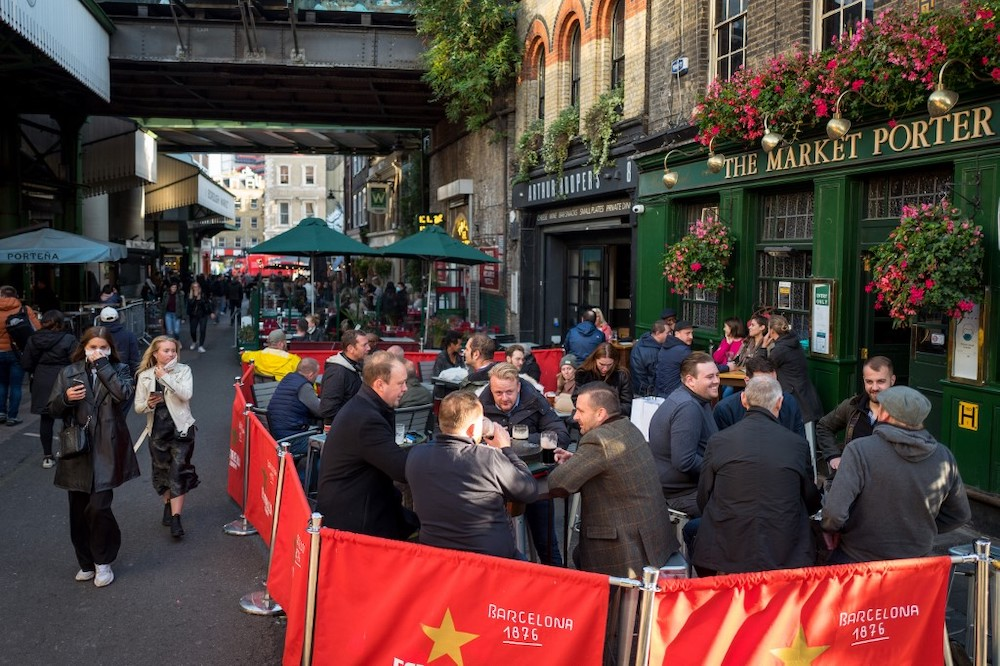 After-work drinkers enjoy a pint outside The Market Porter pub in Borough Market, in London on September 25, 2020, as new earlier closing times for pubs and bars in England and Wales are introduced to combat the spread of the Covid-19. — AFP pic