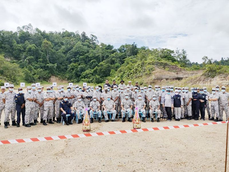 Md Fauzi (centre, seated) in a photo call with MMEA Miri personnel at the end of the competition held at Lambir shooting range. — Borneo Post pic