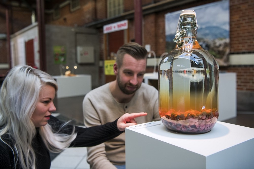 This file photo taken on November 7, 2018 shows visitors reacting to the 'Mouse Wine' from China presented at the Disgusting Food Museum in Malmo, Sweden. Poop wine and scorpion vodka are just some of the stars of a new exhibit on revolting alcohol at