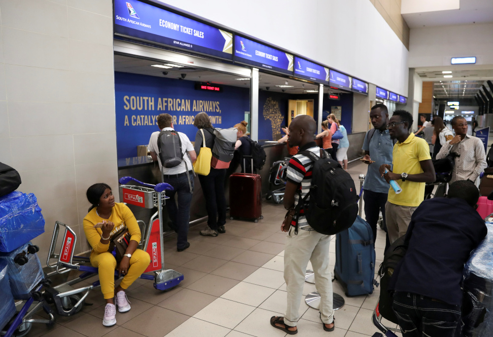 Passengers are seen at the South African Airways (SAA) customer desk at the O.R. Tambo International Airport in Johannesburg, South Africa March 20, 2020. — Reuters pic