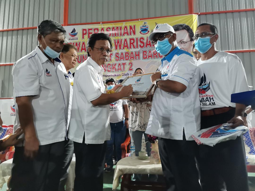 Shafie signing the plaque for the multipurpose hall at Kampung PPRT Sabah Baru Peringkat II. — Borneo Post pic