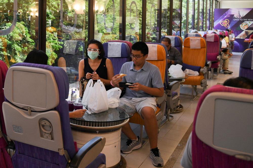 Customers eat at Thai Airways pop-up airplane-themed restaurant at the airlines headquarters with onboard meals prepared by their chefs, while their fleet is still grounded at the airport and the company awaits a bankruptcy court decision, in Bangkok, Thailand September 3, 2020. — Reuters pic