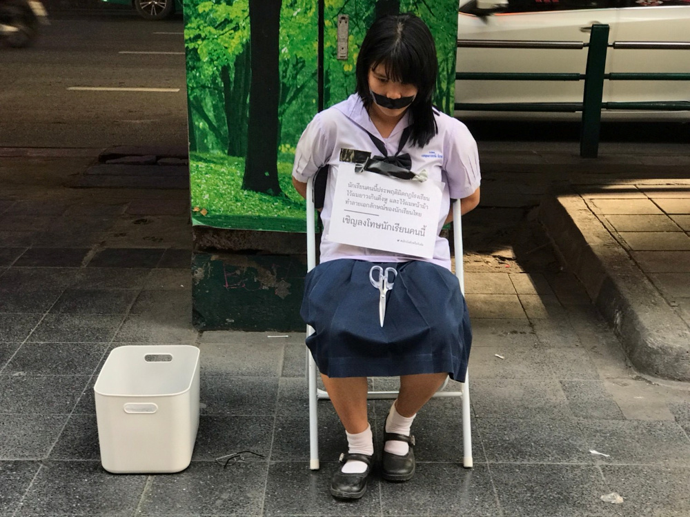 Benjamaporn Nivas, Ploy, stages a protest in a street in Bangkok, Thailand June 28, 2020. The sign reads 'This student has broken the school rule of having long hair and long fringe, tarnishing a Thai student's image. Please feel free to punish her'. — Bad Student handout pic via Reuters