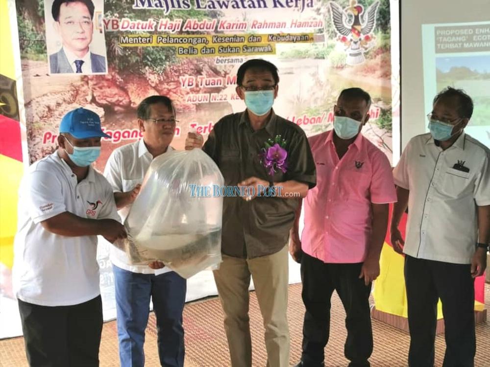 Datuk Abdul Karim Rahman Hamzah (centre) receives a fully grown Semah fish harvested from the tagang project September 13, 2020. — Borneo Post pic
