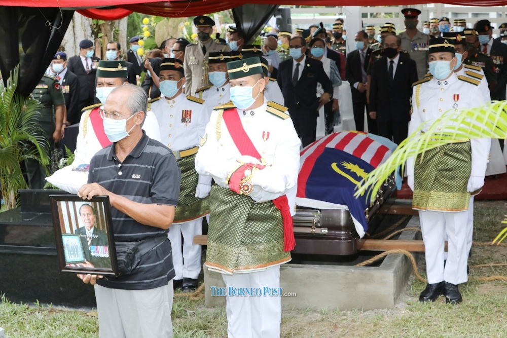 Pall-bearers arriving at the grave site with Datuk Awang Raweng's eldest son Maling holding his father's portrait. — Borneo Post pic