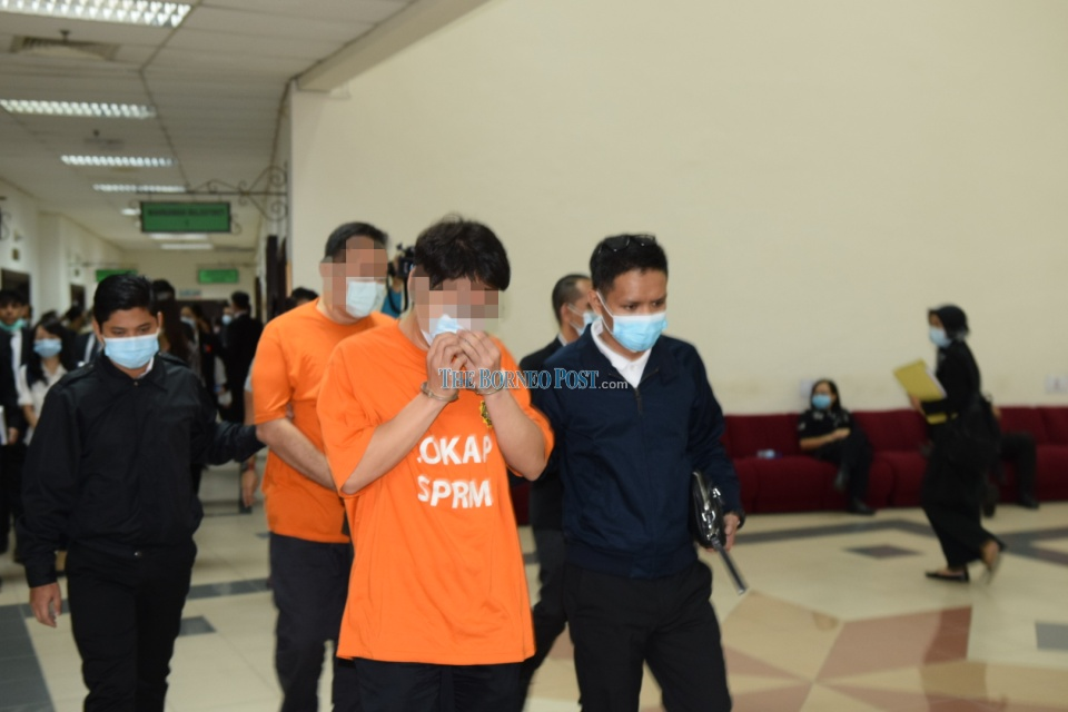 The two suspects being escorted by MACC personnel at the courthouse after the proceeding. — Borneo Post pic