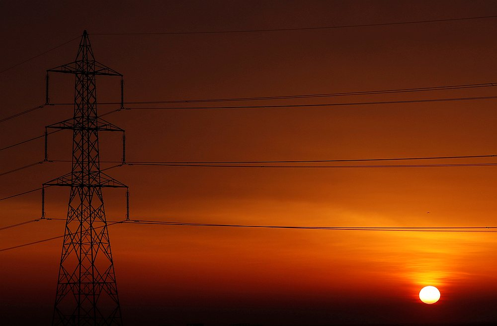 The sun is seen behind high-voltage power lines and electricity pylons at a highway northeast of Cairo, Egypt March 13, 2019. — Reuters pic
