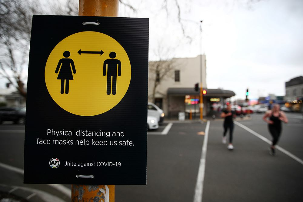 People jog past a social distancing sign as New Zealand's latest Covid-19 safety measure are implemented in Auckland, New Zealand August 31, 2020. — Reuters pic