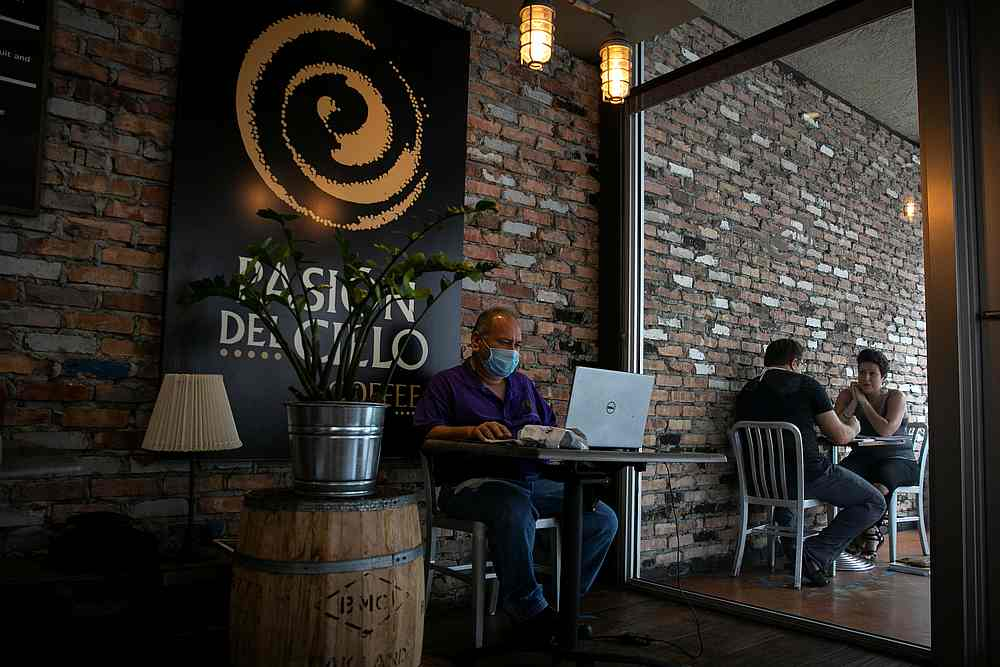 A man works on his laptop inside a coffee shop as Miami-Dade county allows indoor servicing in restaurants after easing some Covid-19 lockdown measures in Miami, Florida August 31, 2020. — Reuters pic