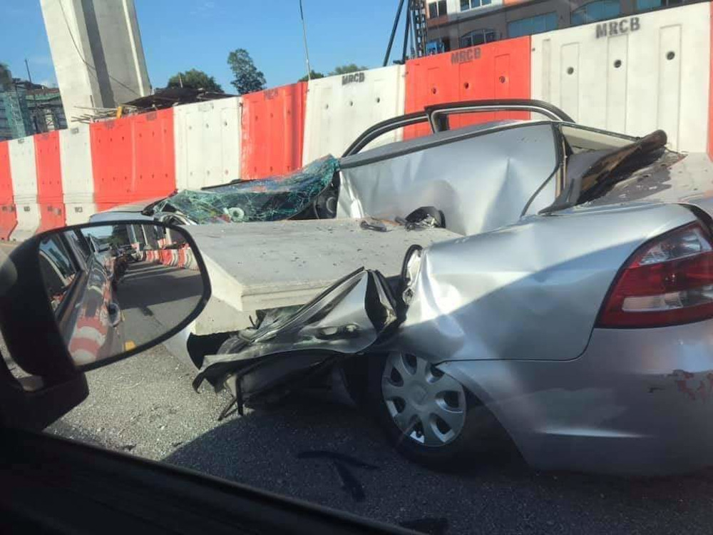 A woman escaped with just an injured left hand when a concrete slab from the construction of the Sungai Besi-Ulu Klang Elevated Expressway (SUKE) fell and hit her car September 19, 2020. — Picture via Twitter/Bernama