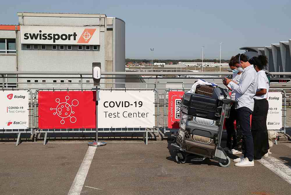 People with luggage use their phones outside a Covid-19 testing centre at Brussels' Zaventem airport premises, allowing travellers to get rapidly tested, in Zaventem, Belgium September 14, 2020 — Reuters pic