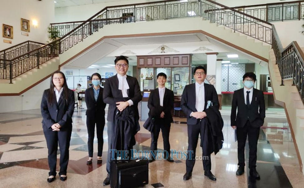 Wong King Wei (3rd left) and members of his legal team after the court judgement. — Borneo Post pic
