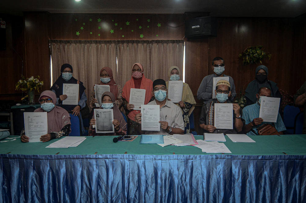 Muhammad Radhi Shariff Hussain with 14 other victims of the travel agency showing their police reports in Butterworth, September 8, 2020. — Bernama pic