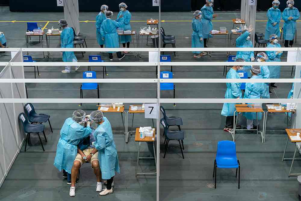 Medical professionals collect samples from a man at the community testing centre for Covid-19 in Hong Kong September 1, 2020. — Pool pic via Reuters
