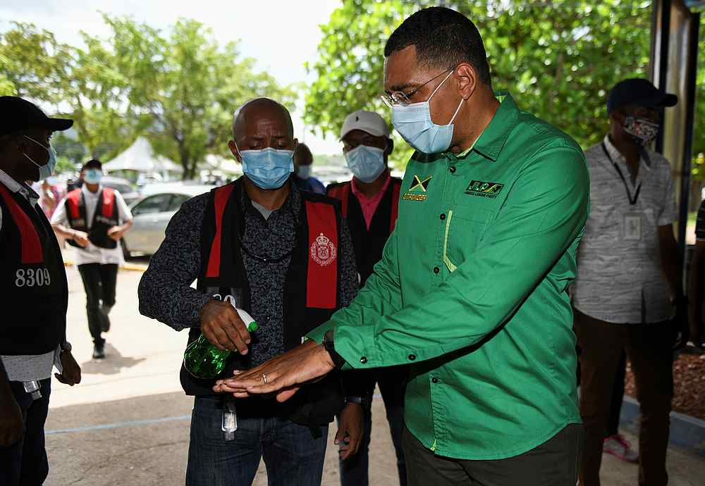 Jamaica's Prime Minister Andrew Holness has his hands sanitised before casting his vote in the general elections, in Kingston, Jamaica September 3, 2020. — Reuters pic
