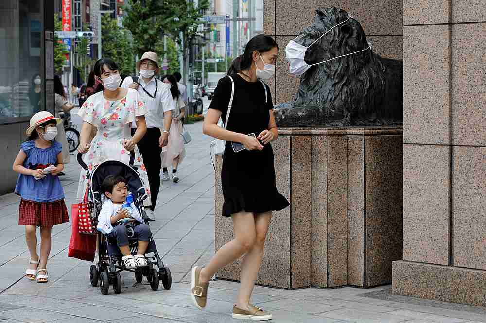 Pedestrians wearing protective masks walk past a statue with a mask on in front of a department store, amid the Covid-19 pandemic in Tokyo August 18, 2020. — Reuters pic