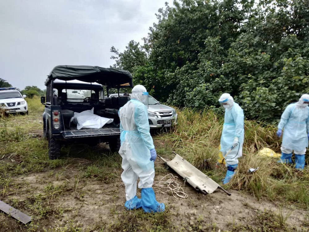 Policemen in personal protective equipment (PPE) suits removing the remains of six drowned Indonesian undocumented migrants at Pantai Teluk C in Bandar Penawar near Kota Tinggi September 20, 2020. — Picture courtesy of the Kota Tinggi district police